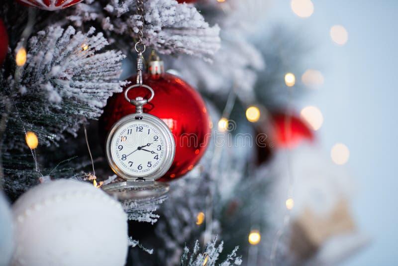 Reloj de plata del vintage que cuelga en el árbol de navidad adornado con el fondo borroso del bokeh imagen de archivo libre de regalías