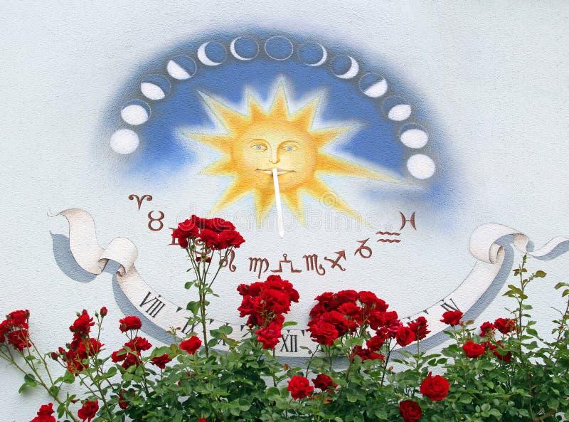 Reloj de sol hermoso y rosas rojas en una pared de la casa imagenes de archivo