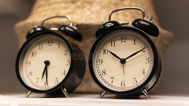 Reloj de tabla negro en el estante contra una cesta de mimbre fotografía de archivo