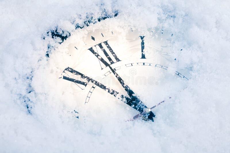 Reloj de tiempo de la Navidad debajo de la nieve foto de archivo