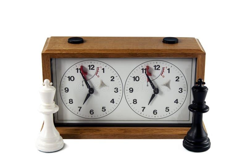 Reloj del ajedrez aislado en el fondo blanco, rey blanco y negro fotos de archivo