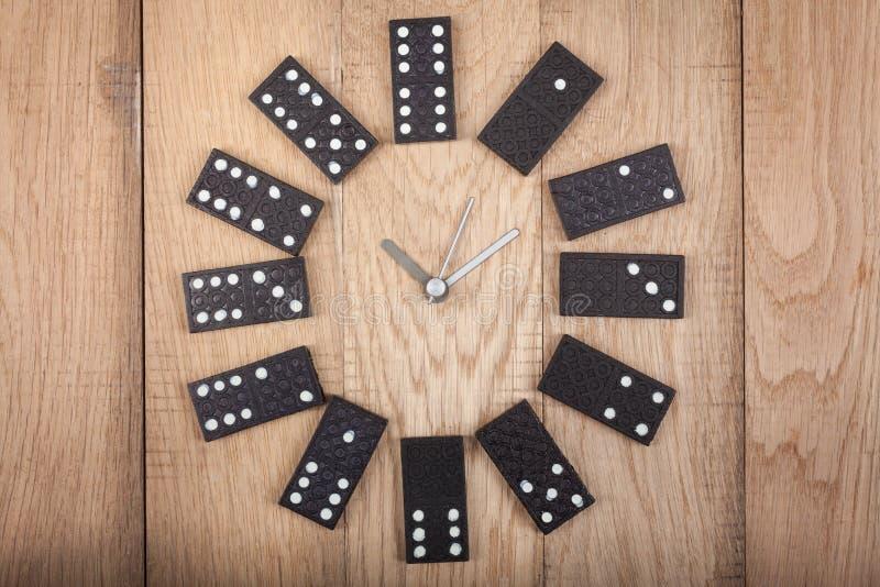 Reloj del estilo del vintage hecho de las placas del dominó en fondo de madera Reloj del dominó imagen de archivo libre de regalías