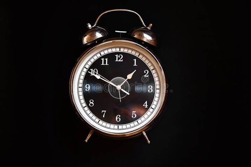 Reloj del hierro con las flechas en fondo negro fotos de archivo
