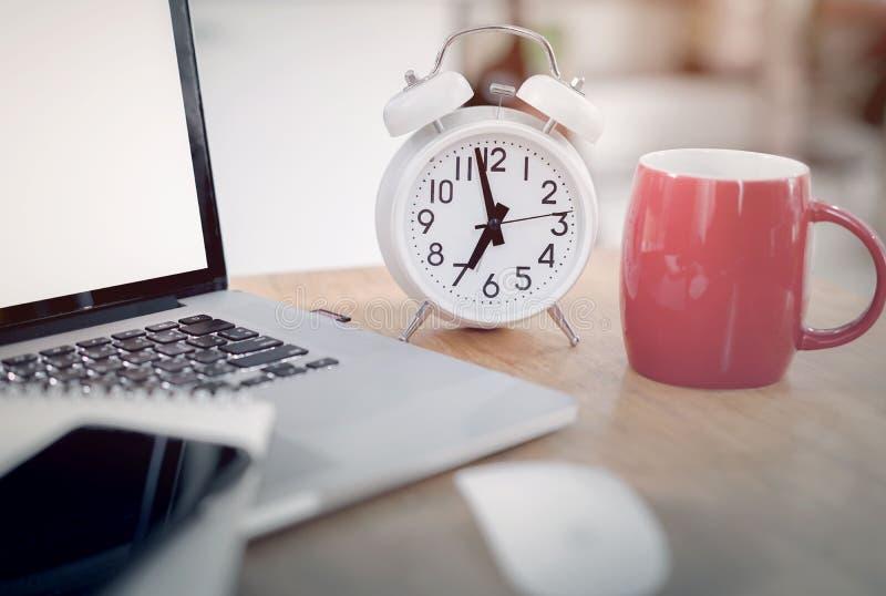 Reloj del primer y taza de caf? roja en el escritorio de oficina imagen de archivo libre de regalías