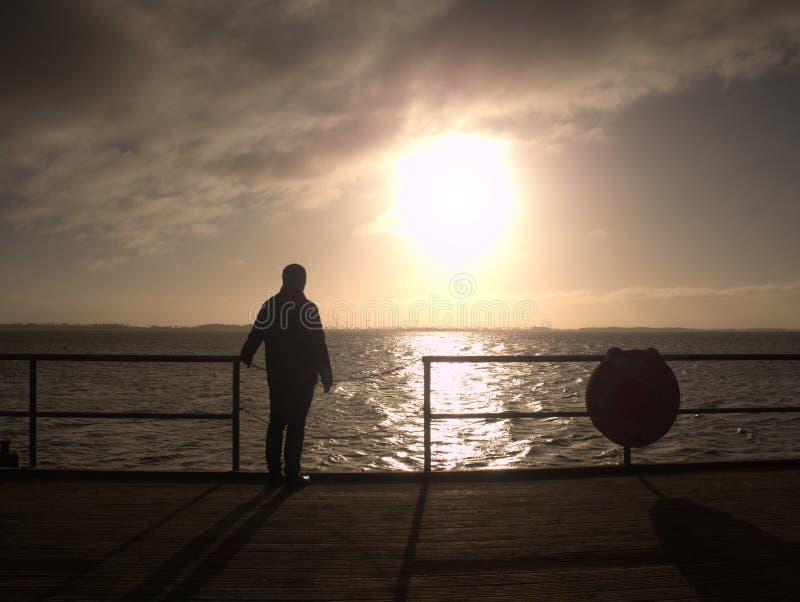 Reloj del viejo hombre el mar de la mañana sobre la barandilla del embarcadero imagenes de archivo