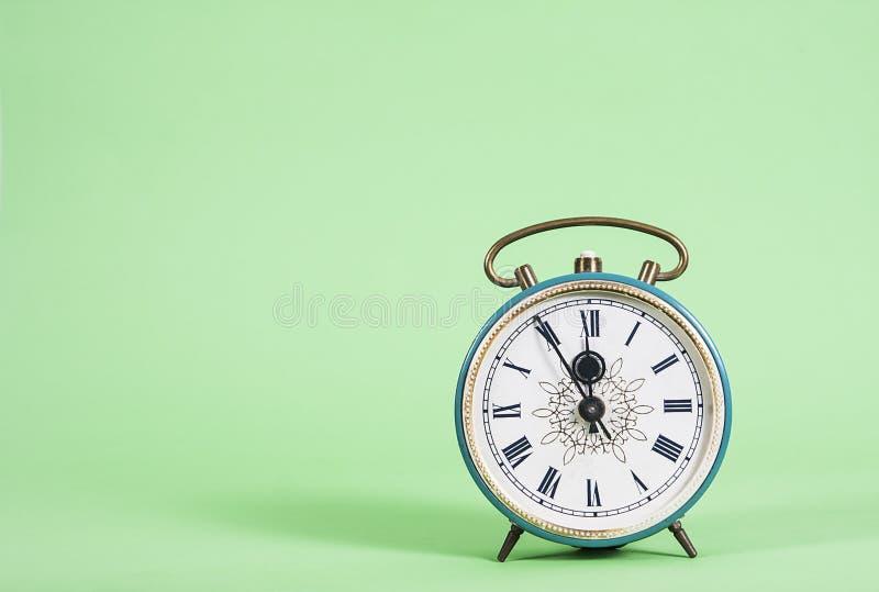 Reloj del vintage que muestra cinco a doce en fondo verde fotos de archivo