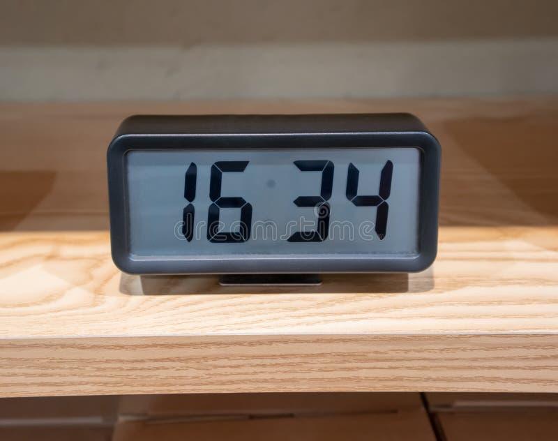 Reloj digital negro con el soporte del metal en estante de madera foto de archivo libre de regalías