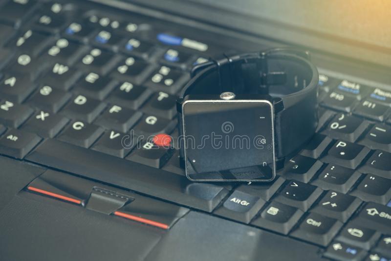 Reloj elegante que pone en un teclado del ordenador portátil fotografía de archivo libre de regalías