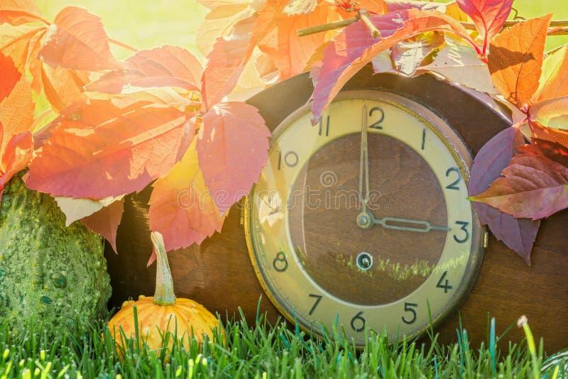 Reloj en las hojas de otoño coloridas como símbolo del cambio del tiempo fotos de archivo libres de regalías