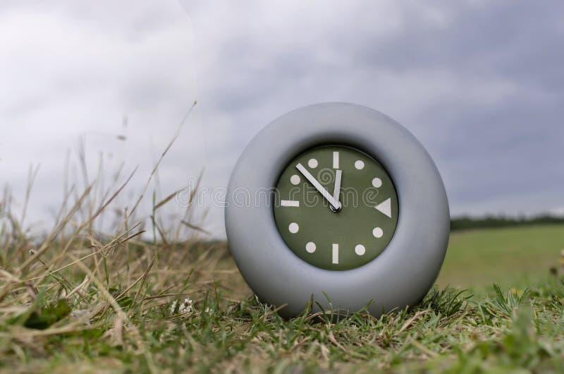 Reloj en un campo foto de archivo