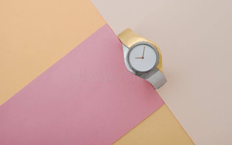 Reloj moderno de la plata y del oro en la opinión de top del fondo del color del rosa y del melocotón fotografía de archivo libre de regalías