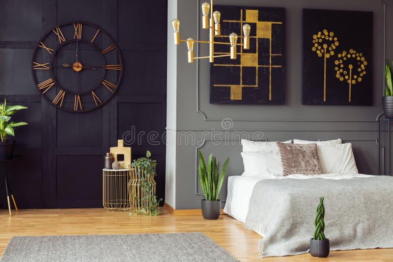 Reloj negro, lámpara de oro, pinturas y cama blanca en un interior elegante del dormitorio Foto verdadera foto de archivo