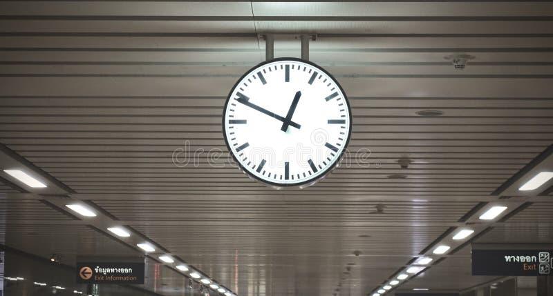 Reloj público en un ferrocarril con el tejado, reloj colgante público clásico blanco y negro, el ferrocarril principal del círcul imágenes de archivo libres de regalías