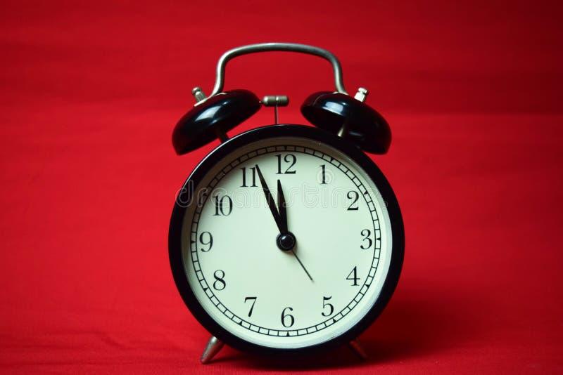 Reloj que hace tictac a las 12 en el fondo rojo fotos de archivo
