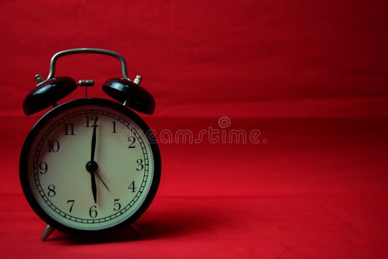 Reloj que hace tictac a las 6 en el fondo rojo fotos de archivo