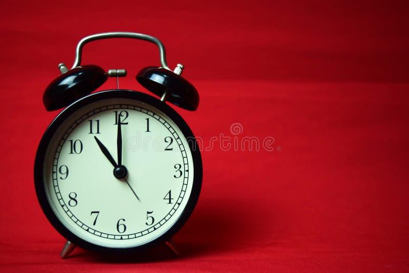 Reloj que hace tictac a las 11 en el fondo rojo imagenes de archivo