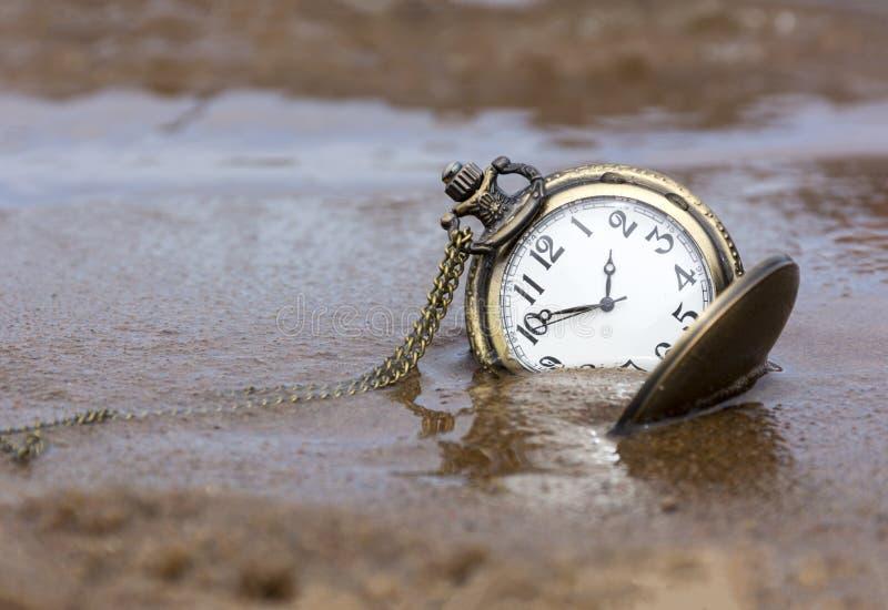 Reloj redondo con las manos que mienten en la arena mojada, agua, tiempo fotografía de archivo