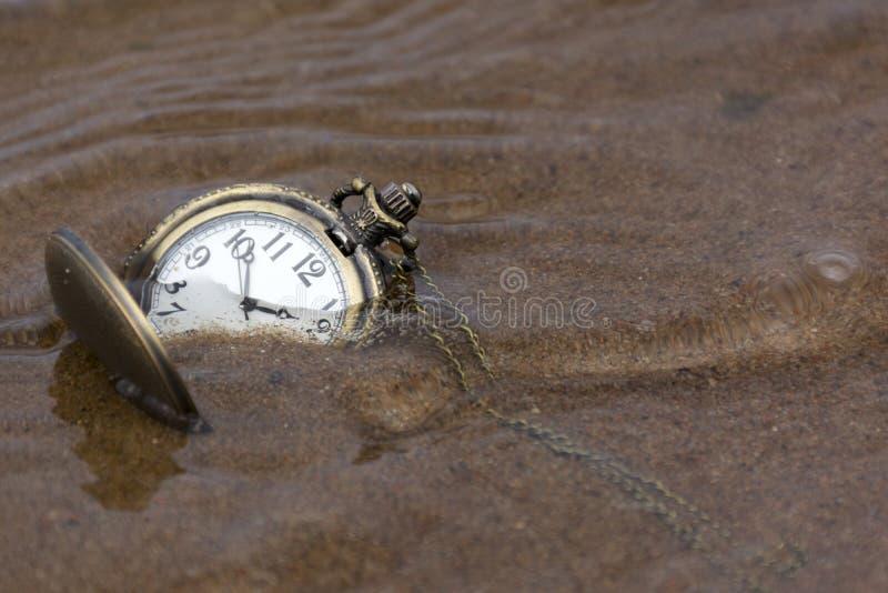Reloj redondo con las manos que mienten en la arena mojada debajo del agua fotos de archivo libres de regalías