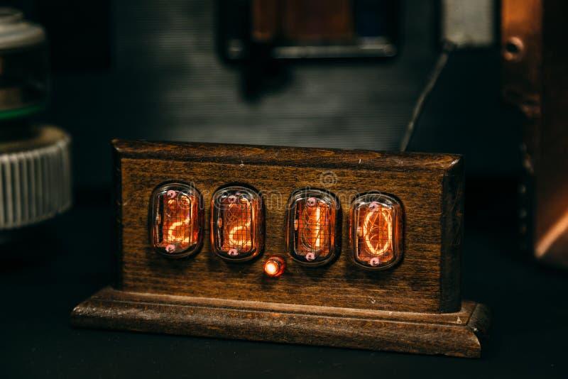 Reloj retro de madera del indicador de la lámpara de Nixie en sitio oscuro foto de archivo libre de regalías