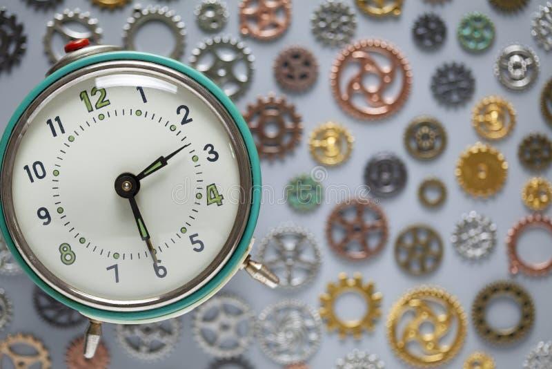 Reloj retro y peque?as piezas del reloj en fondo gris fotografía de archivo