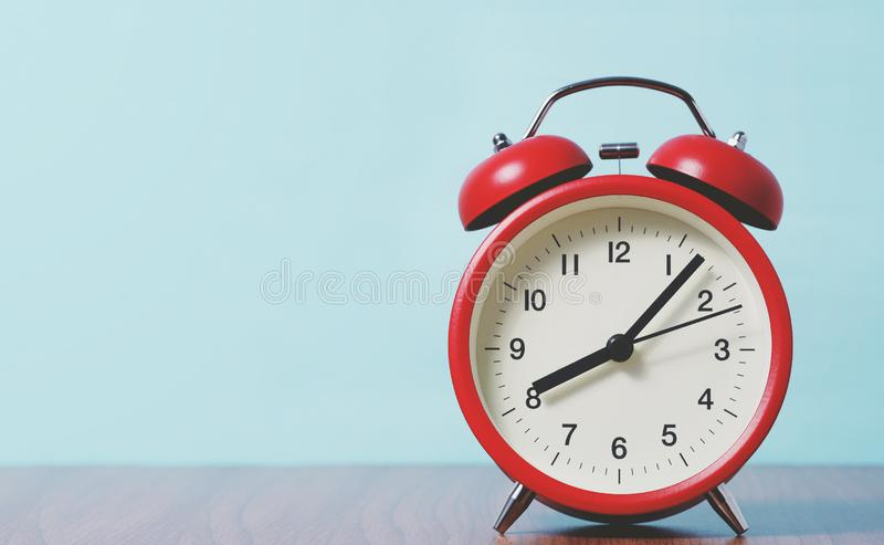 Reloj rojo alarma con fondo azul fotografía de archivo