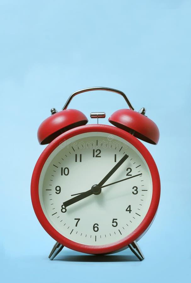 Reloj rojo de alarma con fondo azul claro foto de archivo