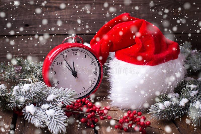 Reloj rojo del vintage, sombrero de Papá Noel, árbol de la piel de las ramas y berrie rojo foto de archivo libre de regalías