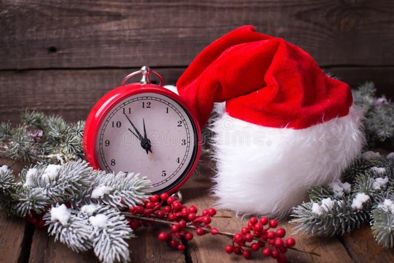Reloj rojo del vintage, sombrero de Papá Noel, árbol de la piel de las ramas y berrie rojo fotografía de archivo