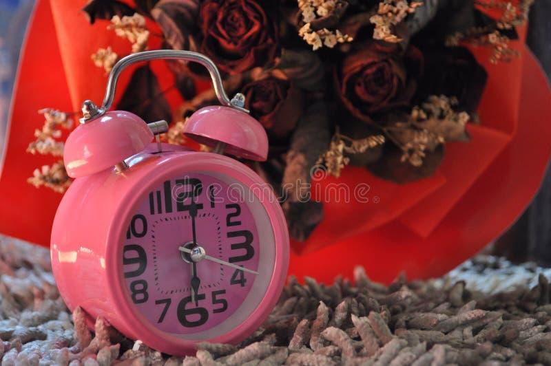 Reloj rosado y rosas rojas secadas fotos de archivo libres de regalías