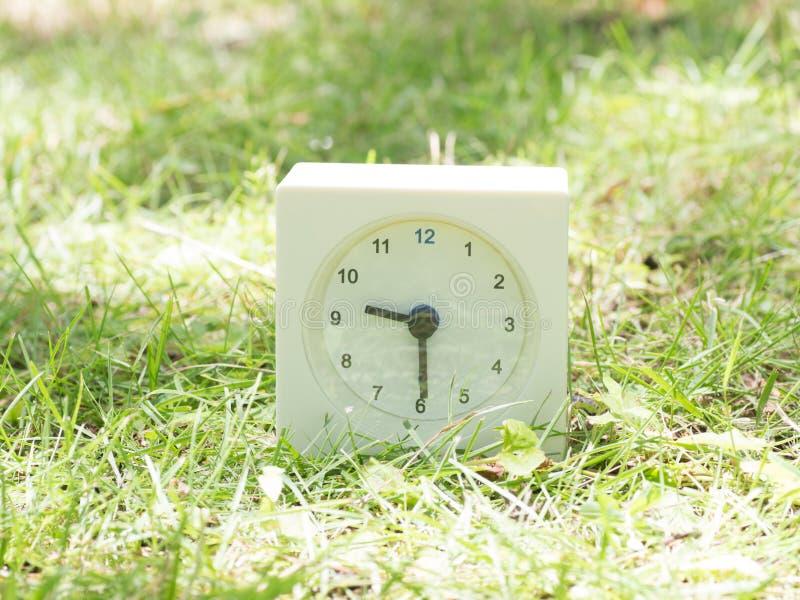 Reloj simple blanco en la yarda del césped, 9:30 nueve treinta medios imagen de archivo