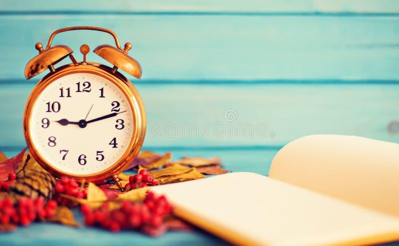 Reloj sobre las hojas del otoño fotografía de archivo