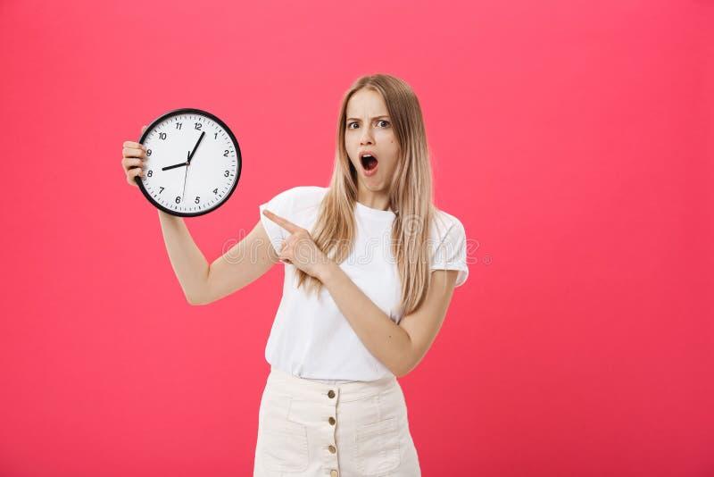 Reloj sorprendente de la tenencia de la mujer La mujer sorprendida en la camiseta blanca sostiene el reloj negro Estilo retro Con imágenes de archivo libres de regalías