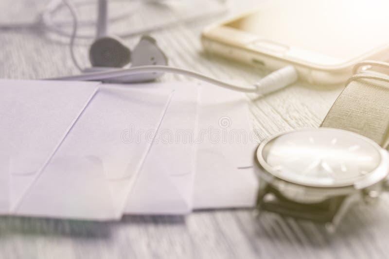 Reloj, teléfono móvil con los auriculares y correo del negocio en una mesa blanca vieja de la oficina fotografía de archivo