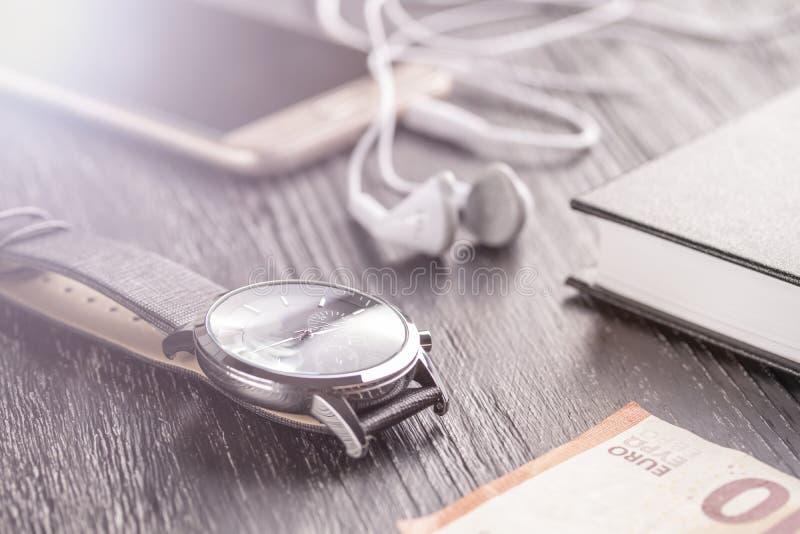 Reloj, teléfono móvil con los auriculares y libreta en la mesa oscura vieja de la oficina Cerca está la nota euro fotografía de archivo
