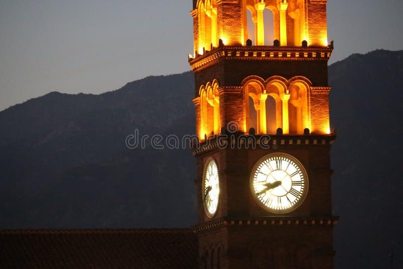Reloj-torre de la iglesia en la puesta del sol fotos de archivo