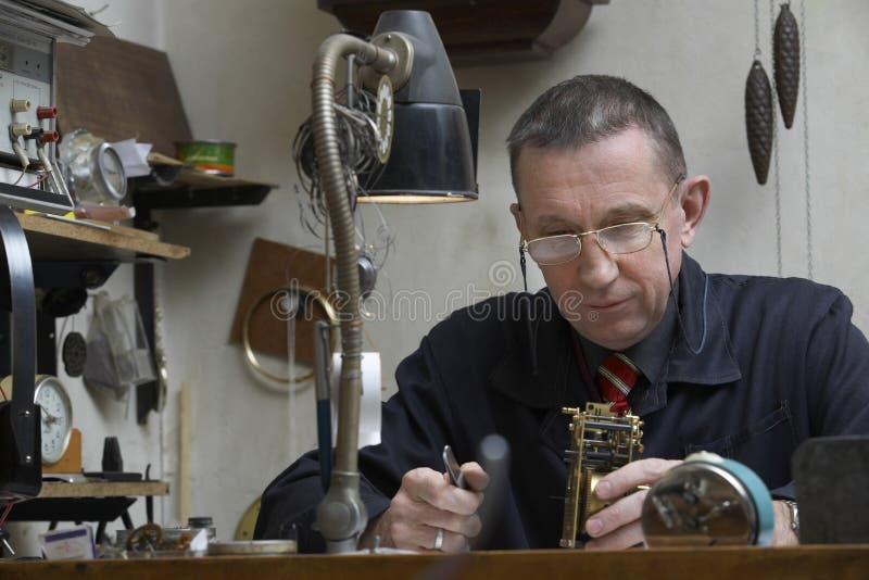 Reloj viejo de Working On An del reparador imagenes de archivo