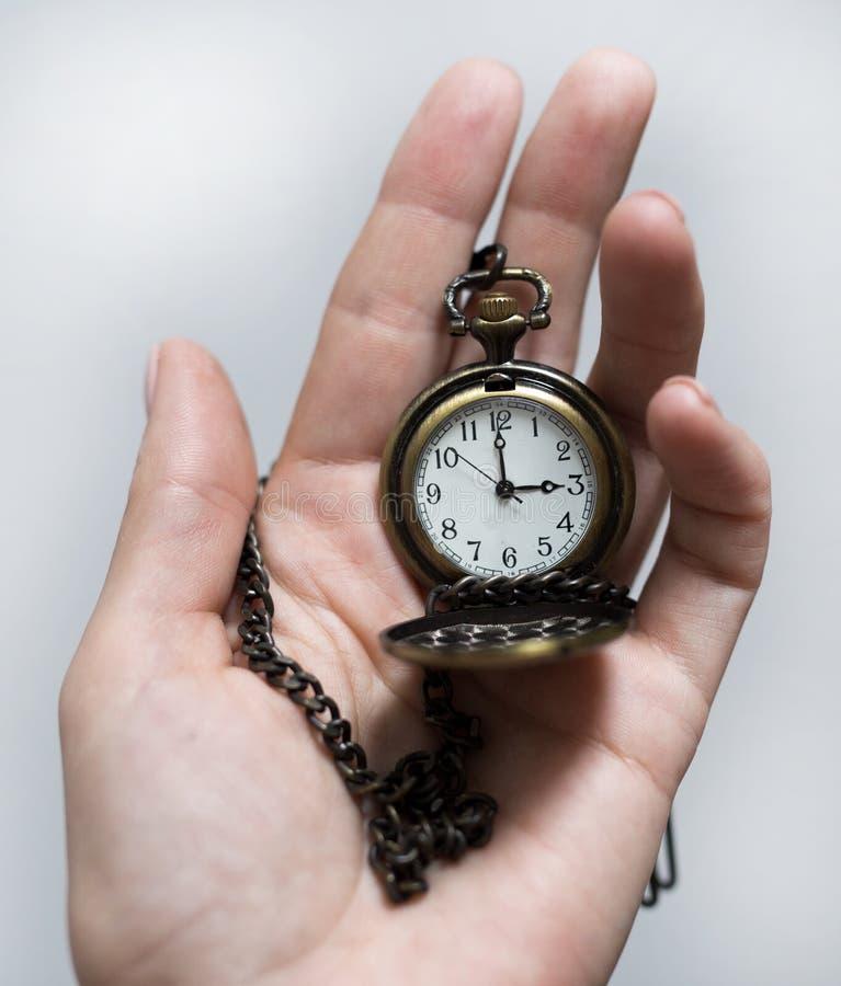 Reloj viejo del vintage en una cadena mano que celebra un reloj en una cadena fotos de archivo
