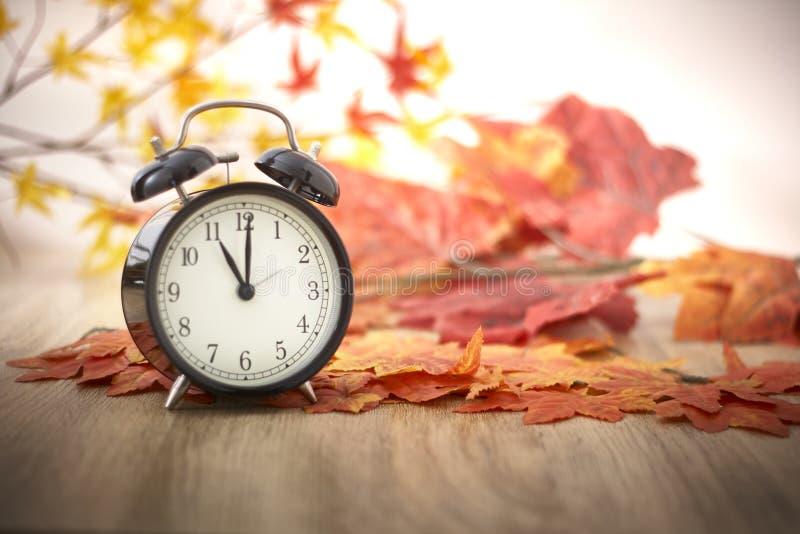 Reloj viejo en las hojas de otoño imagen de archivo