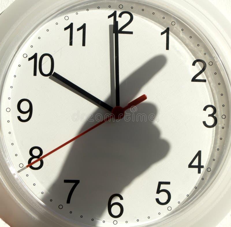 Reloj y la sombra de la mano imágenes de archivo libres de regalías