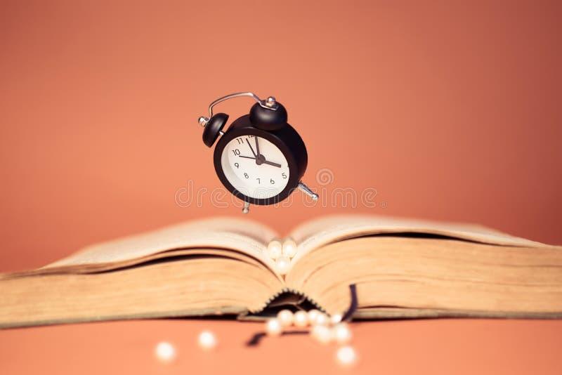 Reloj y libro que vuelan en fondo anaranjado foto de archivo