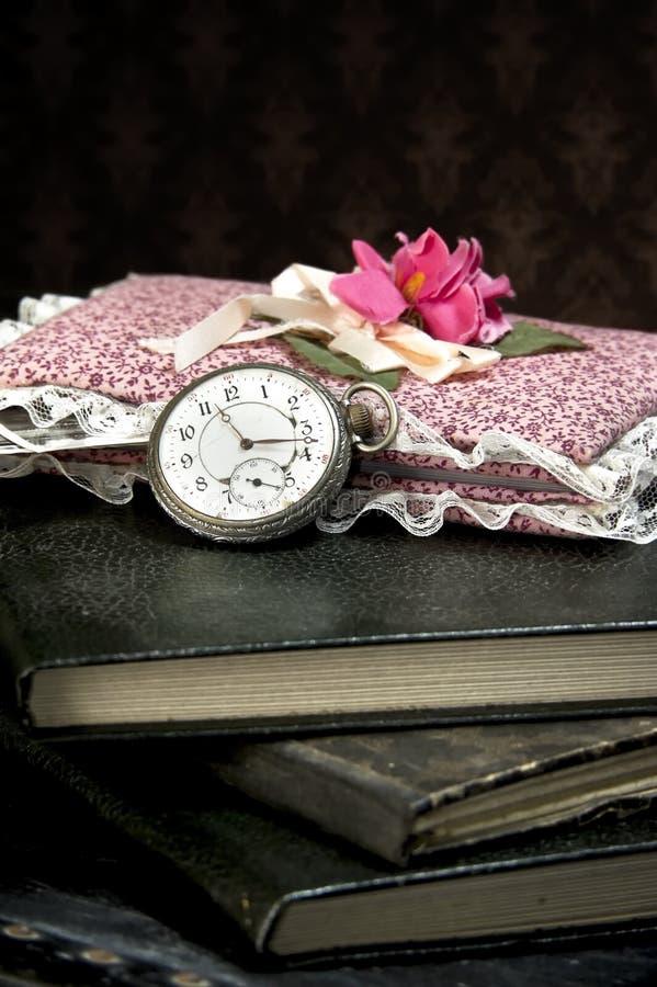 Reloj y libros viejos fotografía de archivo
