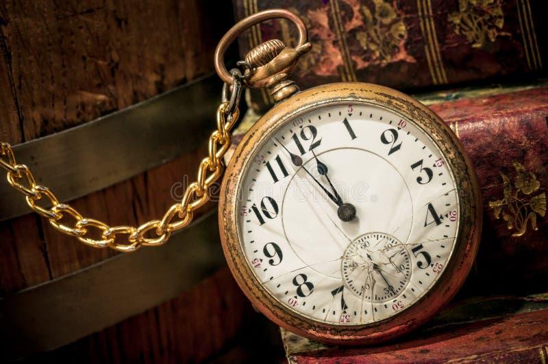 Reloj y libros viejos de bolsillo en oscuro foto de archivo libre de regalías