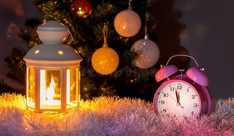 Reloj y linterna con la vela cerca del árbol de navidad a la medianoche ` S Eve del A?o Nuevo Card_ del Año Nuevo y de la Navidad fotografía de archivo
