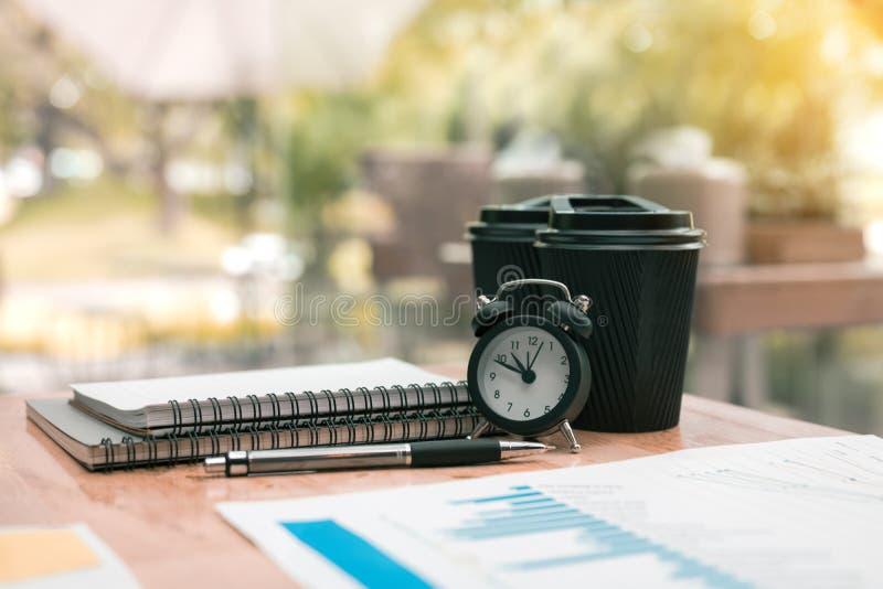 Reloj y materiales de oficina en sitio de la oficina del escritorio imágenes de archivo libres de regalías