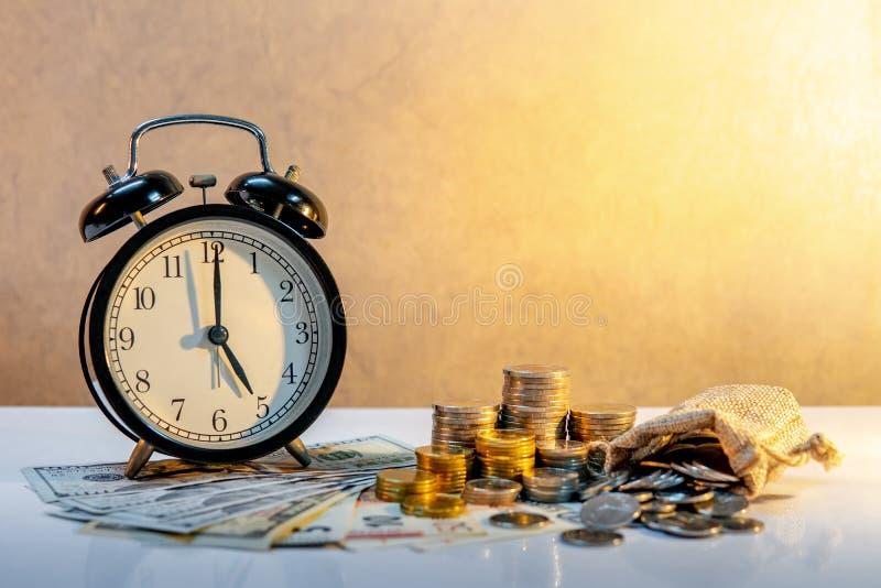 Reloj y moneda en la tabla, concepto de la inversión del tiempo fotos de archivo libres de regalías