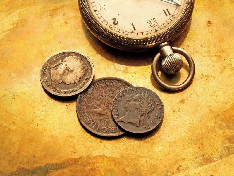 Reloj y monedas viejas fotos de archivo