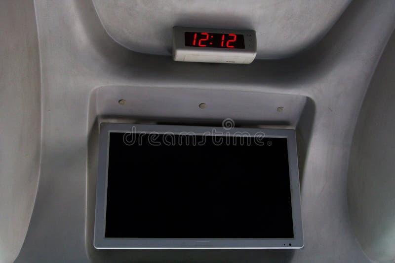 Reloj y pantalla de vídeo en un autobús del viaje fotos de archivo