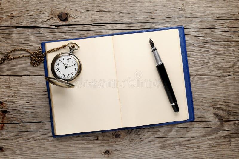 Reloj y pluma en el cuaderno foto de archivo