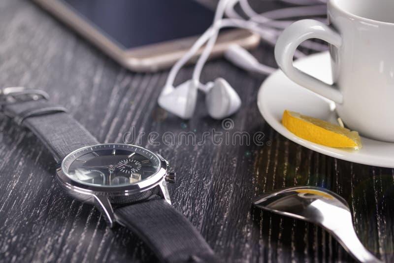 Reloj y teléfono móvil con auriculares y una taza de café en una tabla de madera oscura imagenes de archivo