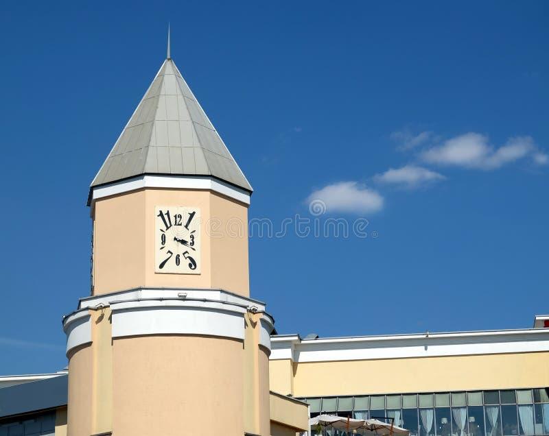 Relojes cuadrados en torre en el edificio beige de la ciudad debajo del cielo azul claro en día soleado brillante imagenes de archivo